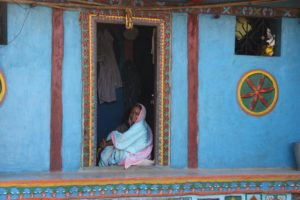 A tribal woman sitting at her door in Purushwadi