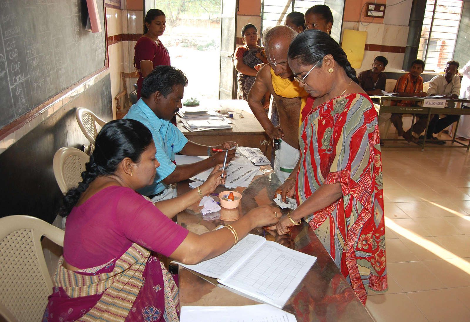 Polling officer administering indelible ink at the finger of a female voter at a polling booth. (Source: Flickr/Public.Resource.Org)