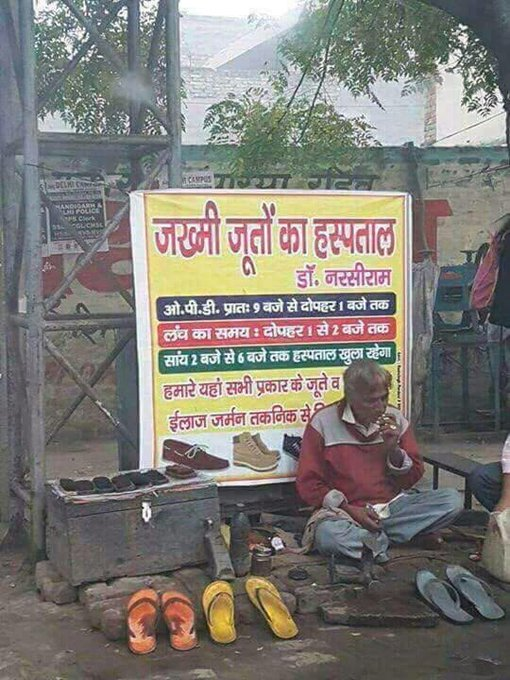 Narsi Ram working at his stall with the billboard behind him which reads 'Zakhmi Jooton Ka Hospital'. (Source: Twitter/Anand Mahindra)