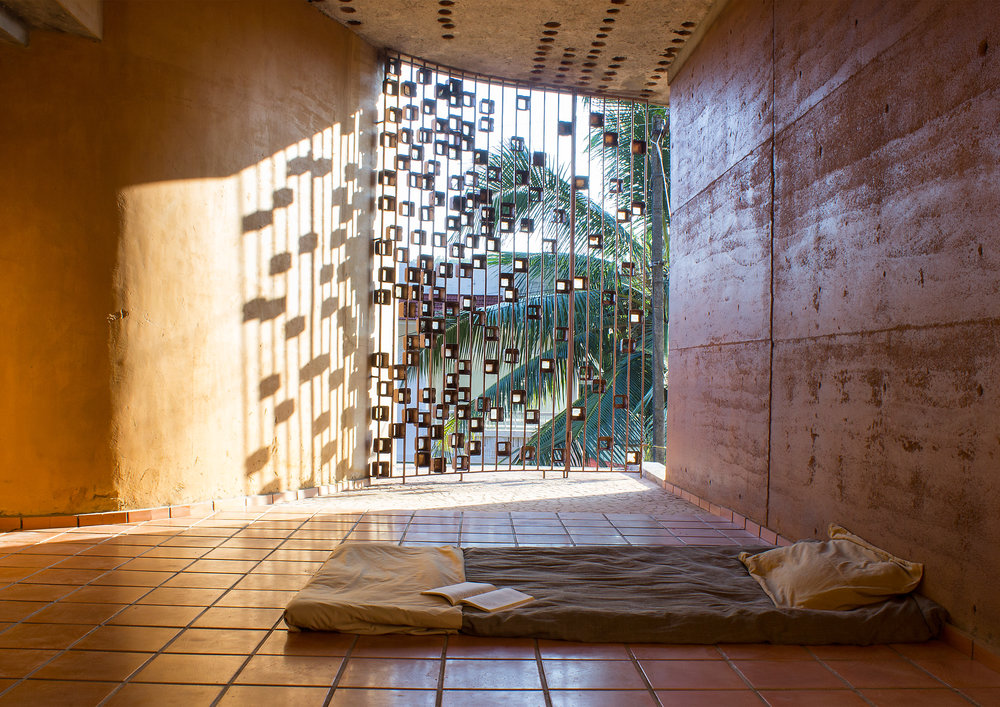 At the Biju Matthew residence site: The windows protected with meter boxes from a local scrapyard create a mural on the rammed earth walls. (Source: Wallmakers)